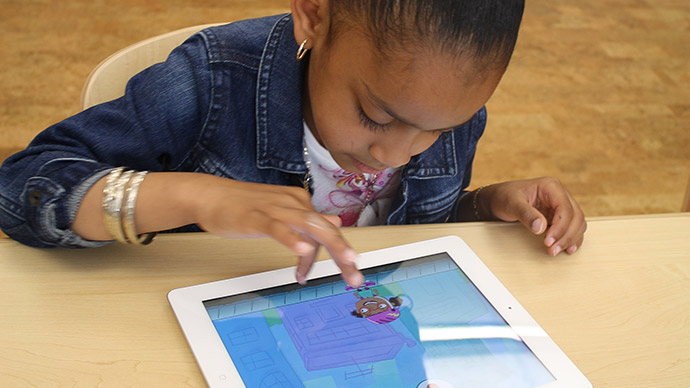 A preschool girl wearing a jean jacket plays the Early Math with Gracie & Friends City Skate app by tapping the screen to make the character in the app jump.