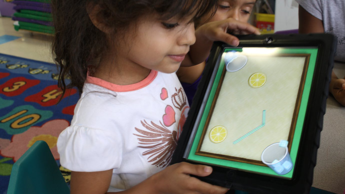 A preschool girl in a white and pink shirt plays the Early Math with Gracie & Friends Lemonade Stand app by tilting her iPad and watching the ice cubes in the app slide into cups.