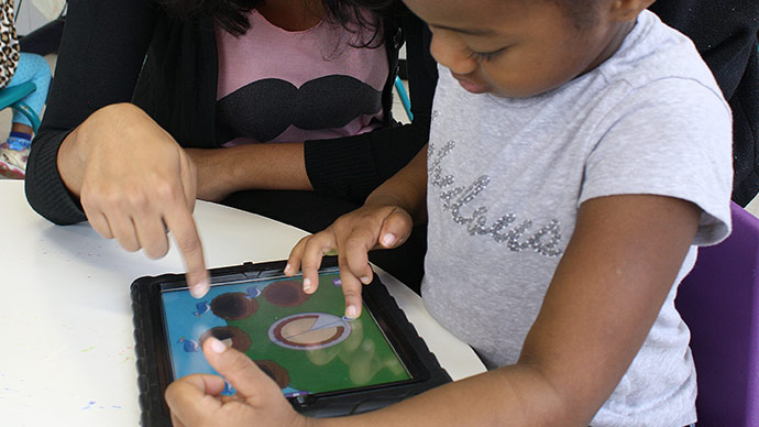 A preschool child in a gray shirt plays the Early Math with Gracie & Friends Photo Friends app and drags a piece of pie while a a teacher sits nearby and points out the birds' nests where the pie should be placed.