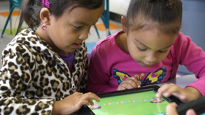 Two preschool girls play the Early Math with Gracie & Friends Treasure Bubbles app, each child with one finger moving characters on the iPad screen.