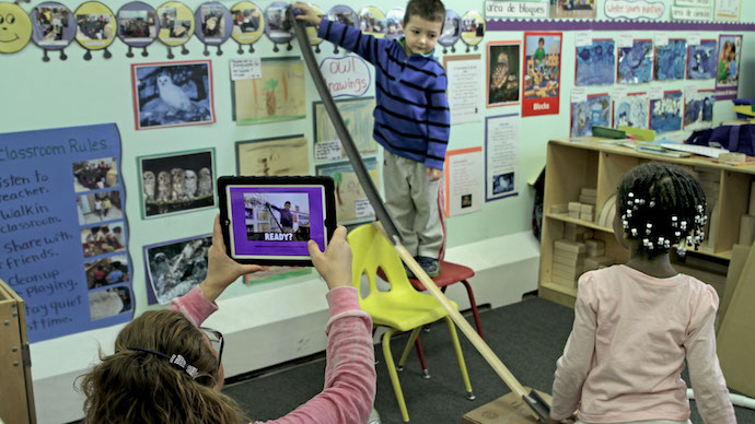 A teacher using the app to film preschool children releasing a ball down a tall ramp.