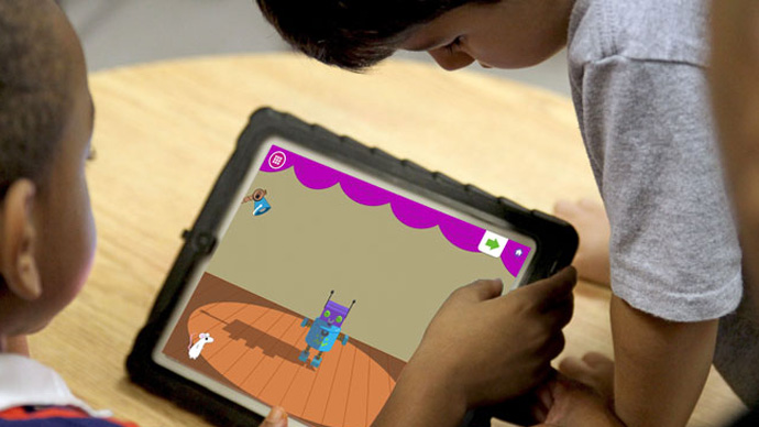 Two preschool boys playing the Shadow Play app by shining lights on a robot.