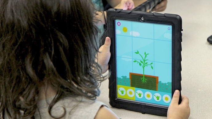 A preschool girl watching a tomato plant grow in the Wonder Farm app.
